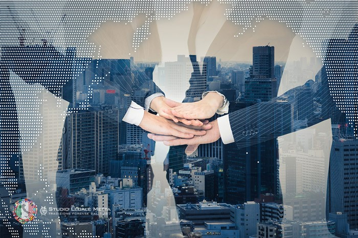 Business men joiniing their hands while in the background there is a picture of a city and the watermark of a world map